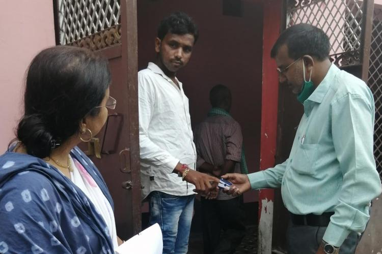 Doctor checks a mans oxygen levels using a finger tip pulse oximeter during a door to door survey to identify spread of the coronavirus disease