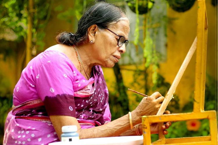 An elderly woman wearing a purple Sari sits sideways to paint a picture in the cosy background of a house courtyard She has her hair put into a lose bun and glasses on her eyes