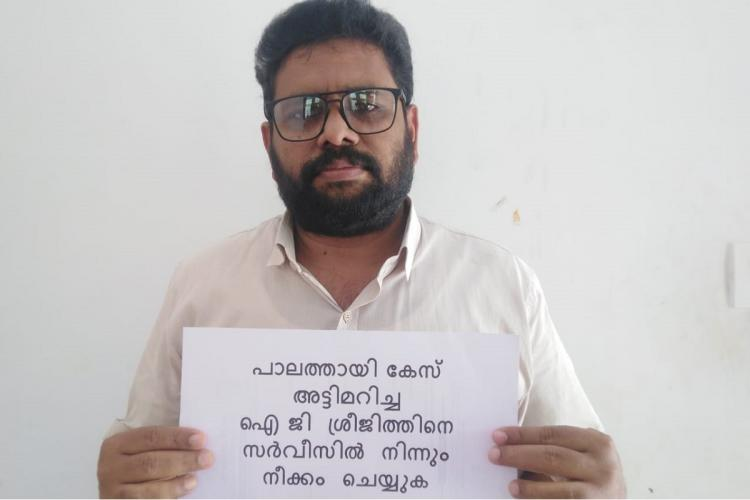 Bearded man wearing specs holds a paper with a message to remove IG Sreejith from the investigation of Palathayi case
