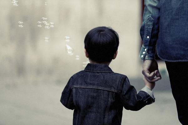 A child is walking hand in hand with an adult their backs are seen