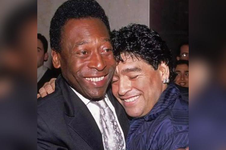 Pela and Maradona are seen hugging each other Pele is wearing a black suit while Maradona is wearing a blue shirt in this image Both are smiling