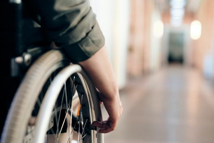 A shot of a persons hand on the wheel of their wheelchair at the end of a corridor