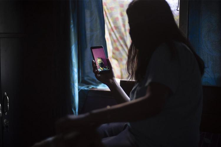 The silhouette of a woman talking to her father in video call during the lockdown