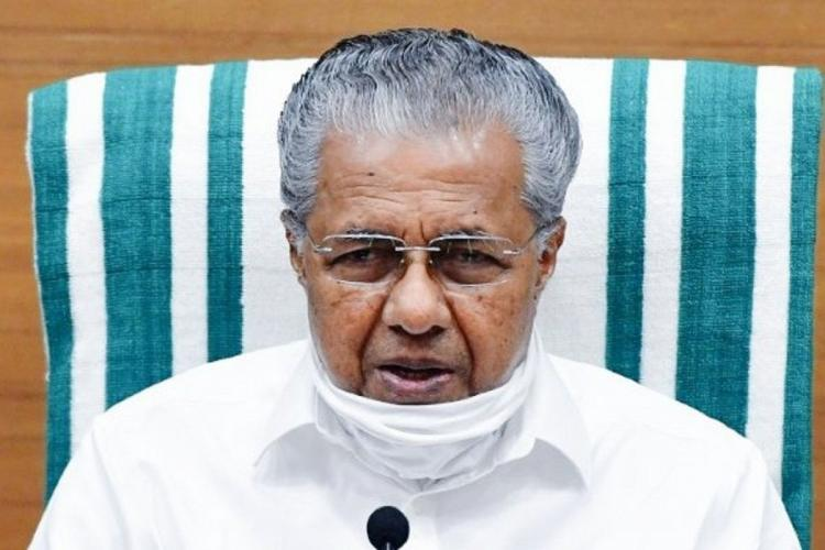Pinarayi Vijayan with mask on chin sits in front of a microphone