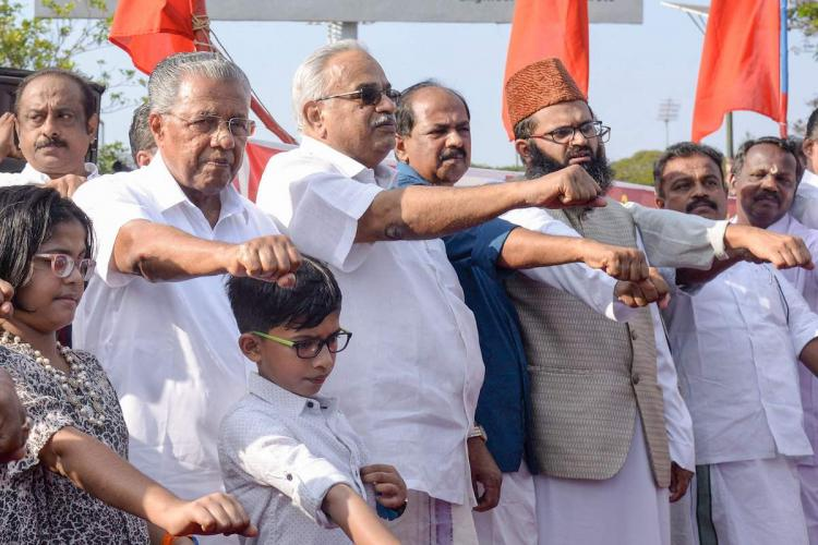 Kerala Chief Minister Pinarayi Vijayan with his right hand stretched out to take an oath, surrounded by several people in a similar stance including two children.