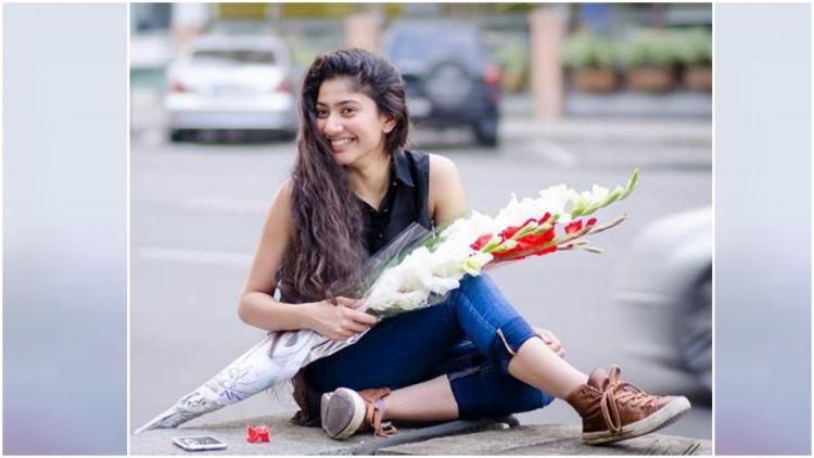 Actress Sai Pallavi holding a boquet in her hands and sat on the road posing for a picture