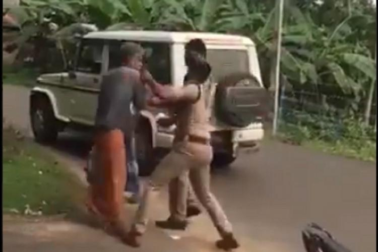 An elderly man is being manhandled by a policeman as another police man can be seen behind him and the police jeep as well It is the roadside