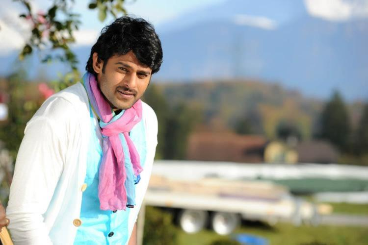 Prabhas in a blue t shirt and white jacket wearing a pink scarf