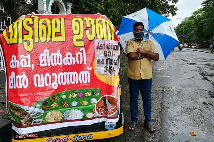 An auto rickshaw driver stands next to his rick which is covered in a banner about meals he sells and he is under a blue and white umbrella