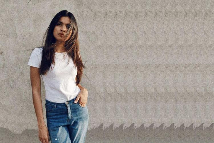 Young slender woman in white T shirt and blue jeans stands looking away Her straight hair is on either side of her face falling on her T shirt and her right hand is in the front pocket of the jeans