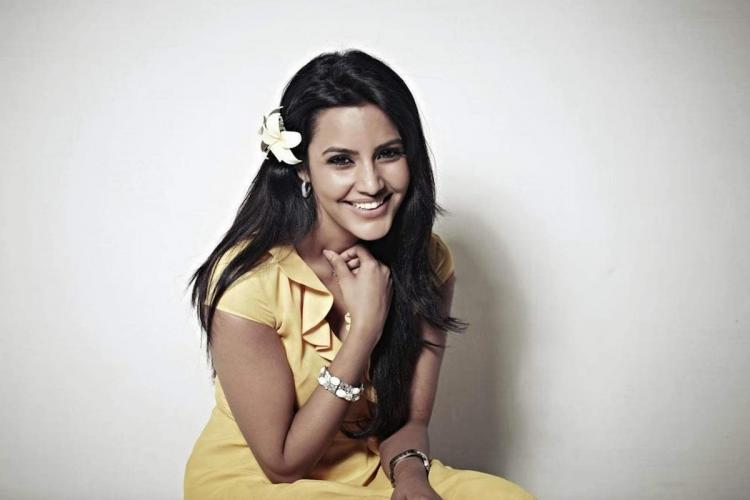 Priya anand smiling wearing yellow dress with a flower in her hair