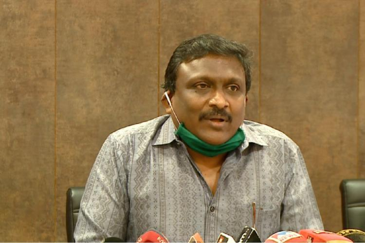 Renjith M in grey shirt has a green mask under his chin and a number of microphones in front of him Its a brown background