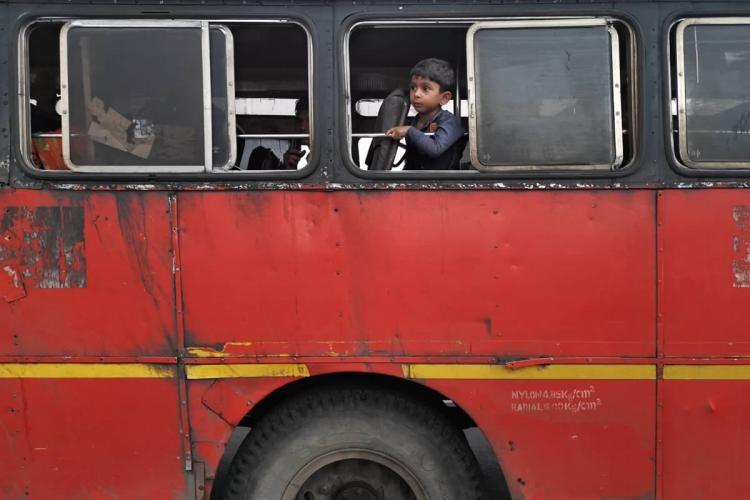 A small boy in a navy blue shirt looks out from the window of a red government bus