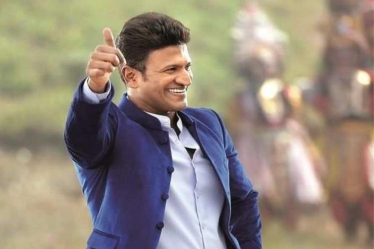 Puneeth Rajkumar in a blue coat doing thumbs up