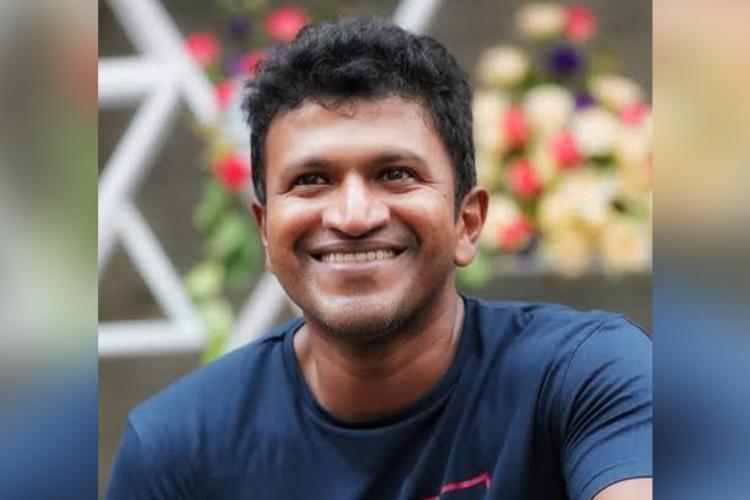 Puneeth Rajkumar looking away from camera and smiling