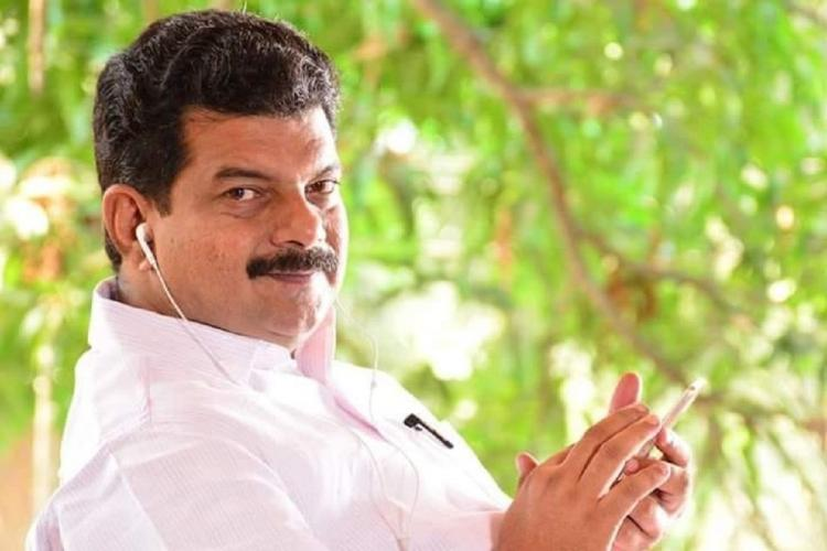 PV Anvar in white shirt sits sideways and faces the camera He has plugged on ear phones and has his hands over his phone There is a green tree in the background