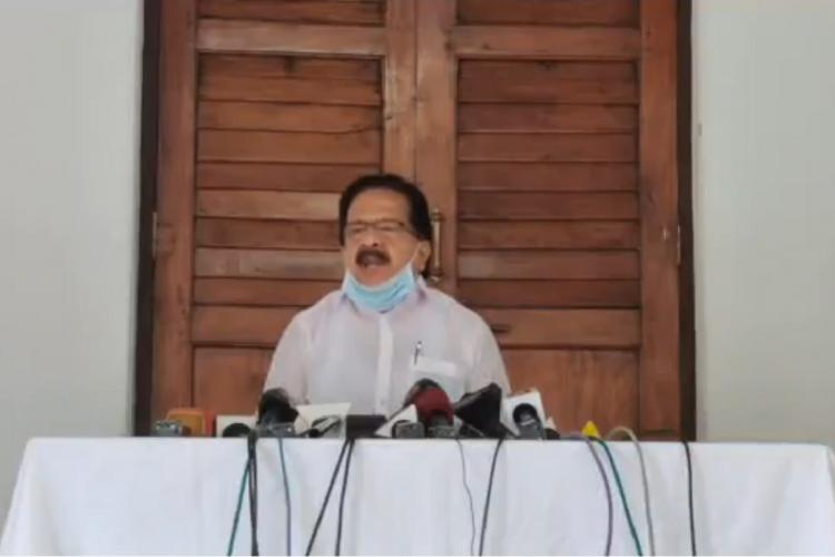 Ramesh Chennithala sits facing a few microphones placed on a table covered in white as he talks to the press with his mask under the chin There is a closed door behind him