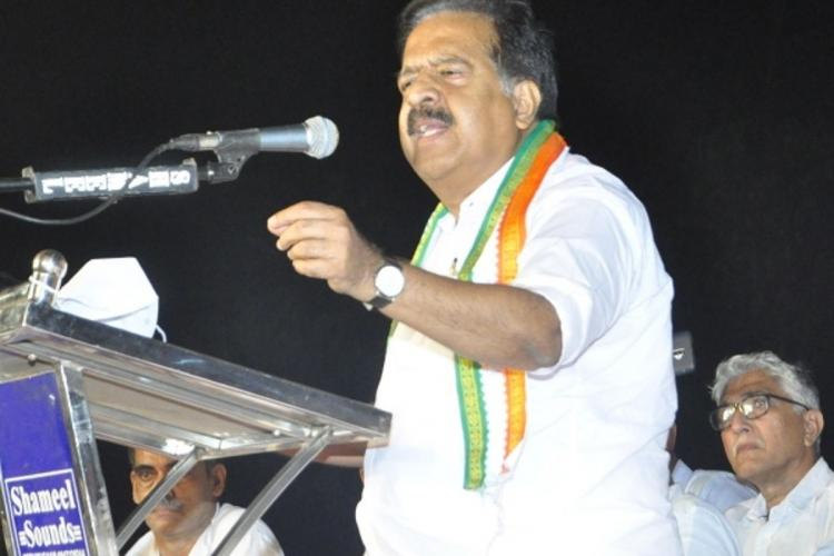Kerala Opposition Leader Ramesh Chennithala speaking in a meeting facing mike raising his right hand