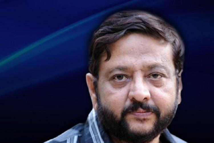 A close-up photo of Bengaluru-based journalist and founder of Hai Bangalore tabloid Ravi Belagere. He is wearing a blue checked shirt and looking unsmiling at the camera.