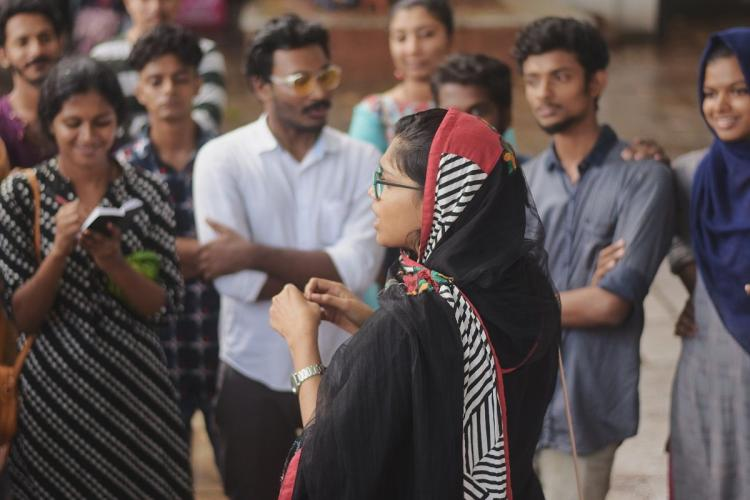 Students circle a member of Red Cycle an initiative to start conversations on menstruation