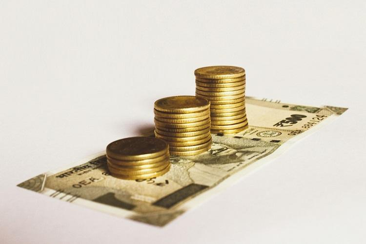 A stack of coins above a 500 rupee note