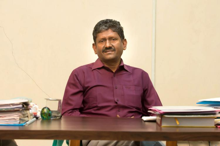 U Sagayam an IAS officer who took voluntary retirement in October 2020 wearing a maroon shirt and looking directly into the camera Hes seated at a desk and there are files on his table