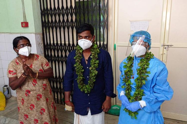 Sarath and Abhirami get married at a COVID-19 ward in Alappuzha Medical College Hospital Sarath is wearing a navy blue shirt with white mundu and mask Abhirami is completely geared in a PPE kit Both are wearing garlands Saraths mom wearing a mask is also seen in the image