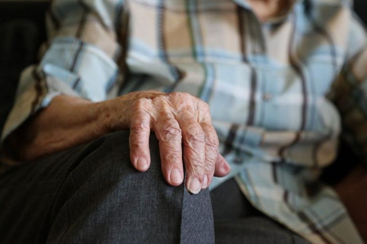 Hands of an elderly man placed on his knees