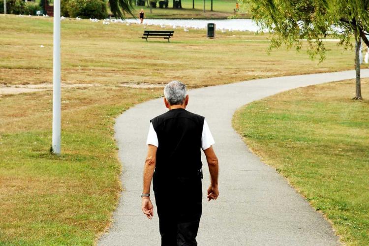 Senior citizen wearing black trousers and black vest walking along a path