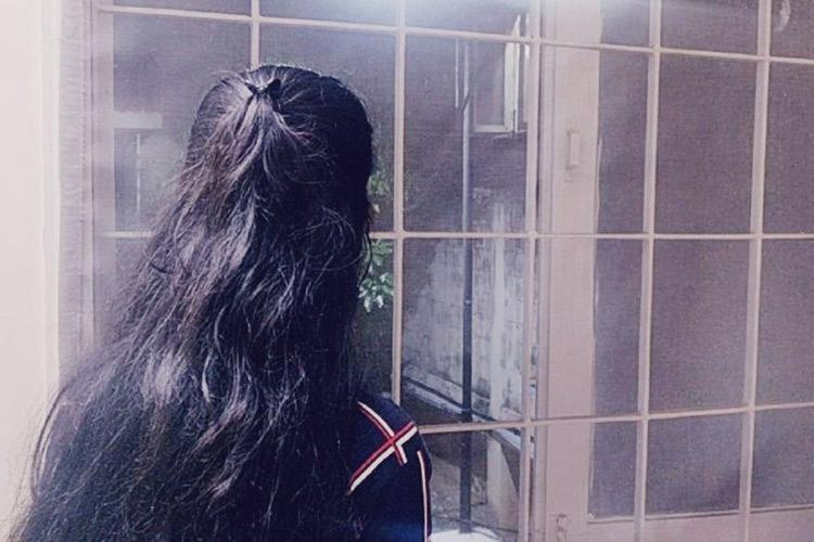 A picture of a woman from behind She has long hair and is looking outside a window