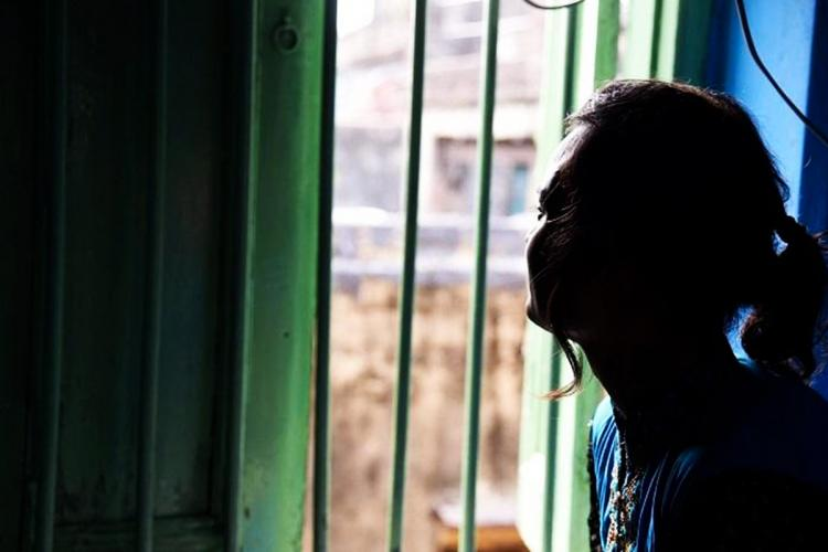 Silhouette of a woman staring out of a window