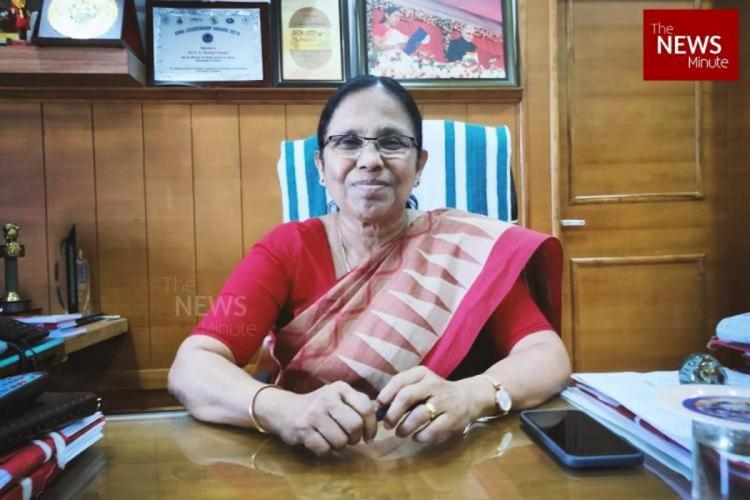 Kerala Health Minister KK Shailaja at her desk smiling directly at the camera She is wearing a beige and red saree with a red blouse