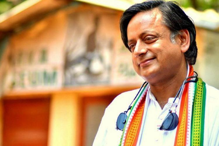 Tharoor wearing white kurta and the Congress shawl over it looks sideways and smiles sun shades hanging around his neck