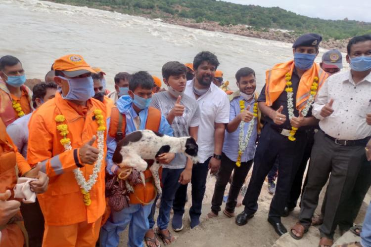 The rescued shepherd is visibly shaken as he holds his dog The male rescuers who wear highly visible orange clothes around him are joyful as they pose for the camera wearing flower garlands and shawls in appreciation
