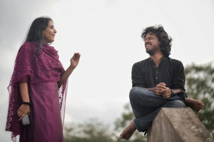 Shruthi in maroon salwar had a hand raised as she talks to Sooraj who is in black shirt sitting on a step and laughing