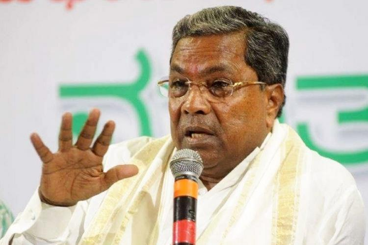 Siddaramaiah addressing a presser He is wearing a white shawl with a golden border and gesturing with his right hand