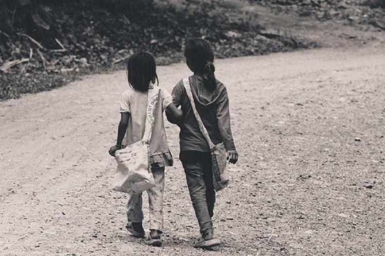 Representative image of two young children walking on a road with bags over their shoulders