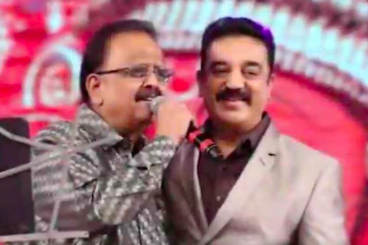 SPB and Kamal Haasan embracing each other on stage during a live event