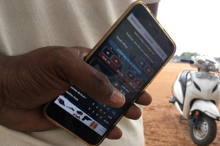 A man holding a phone with match stats open