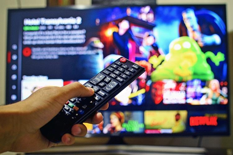 A TV with netflix open in the background In the foreground a person holding up a remote to the TV
