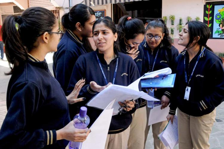 Students discuss the question paper after appearing for an exam