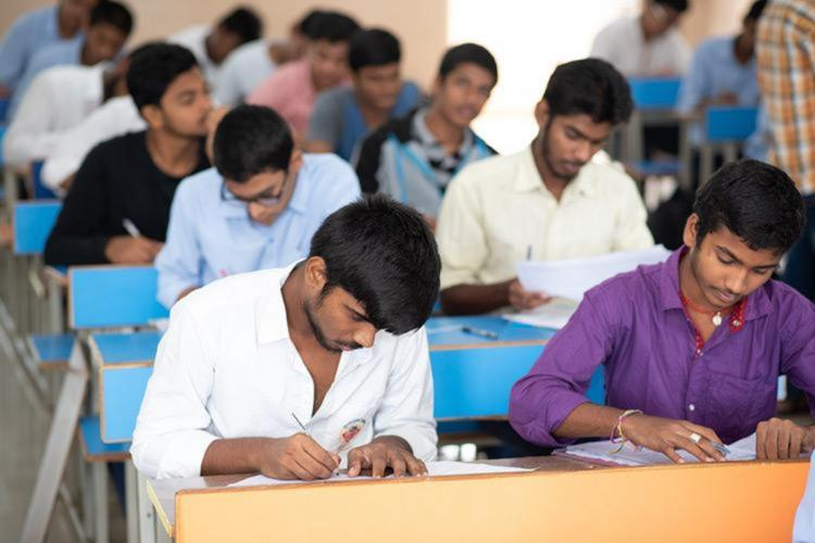 Students sitting at desks and writing an exam