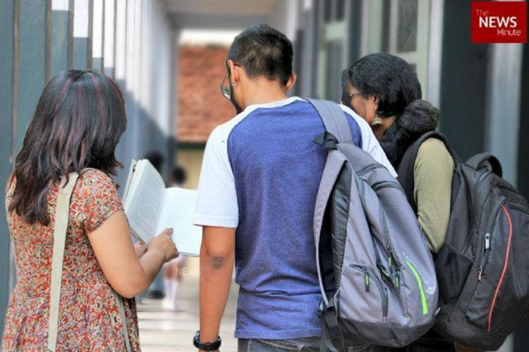 Three students standing in a corridor of a college building carrying bags and looking into a book
