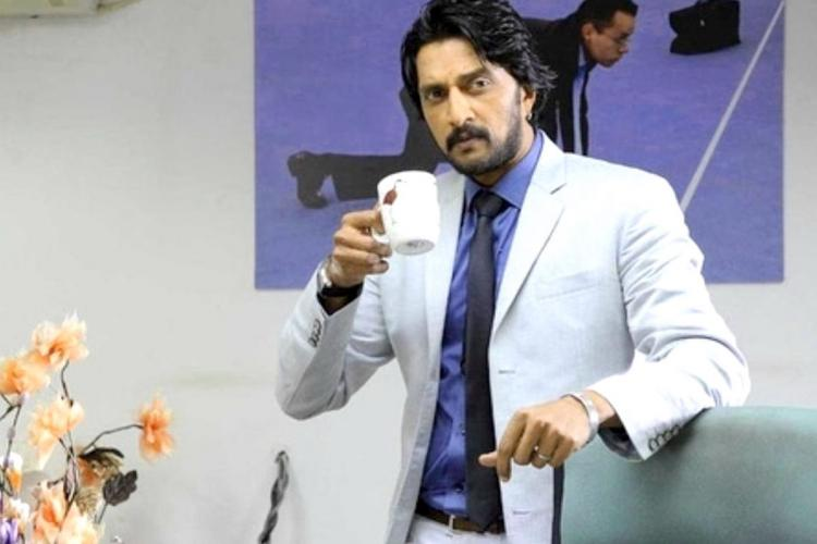 Kichcha Sudeep wearing a grey suit and holding a cup