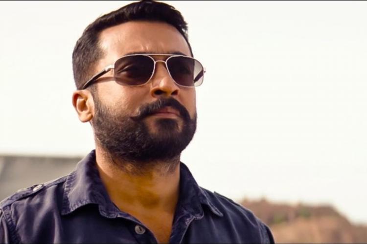 Actor Suriya in a still from Soorarai Pottru wearing sunglasses and looking ahead