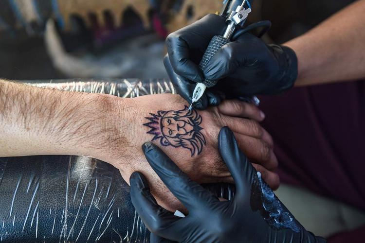 tattoo artist making a tattoo on a customer's hand