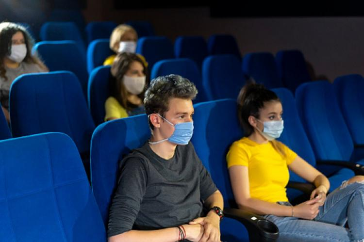People seen seated in chairs in a theater by wearing masks