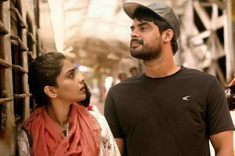 Aishwarya stands leaning towards a train and looking sideways to Tovino who is wearing a cap and looking inside the train