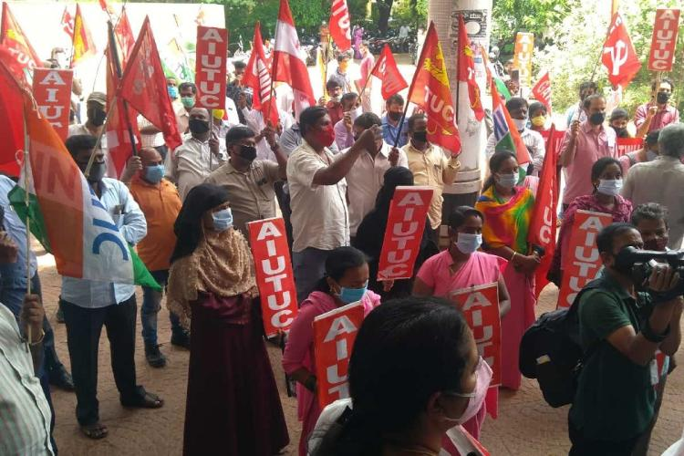 People holding red flags stand in protest against labour law changes