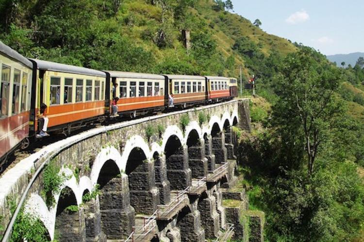 A train that is painted orange in colour is moving across a bridge The bridge is over a water body and has arches